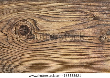 Old plank, with wood knots and cracked, layered rough surface, separated by annual growth lines. - stock photo