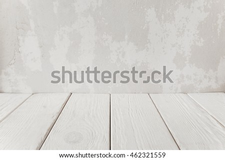 Old plaster wall with white wooden floor, close-up. Abstract empty interior background, free space