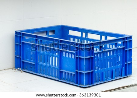 Old plastic crate with white bowl. - stock photo