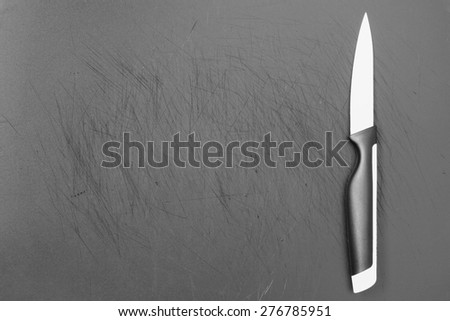 Old plastic cutting board black. Scratches on the knife. - stock photo