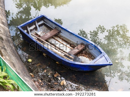 Old plastic rowboat in the pond of urban park. - stock photo