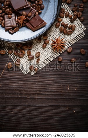 Old plate on canvas with coffee beans, spices and chocolate pieces, wooden background - stock photo