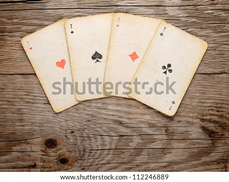 Old playing cards on wooden background - stock photo
