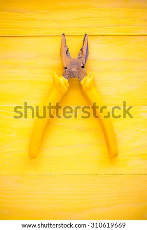 Old pliers on the yellow wooden surface - stock photo