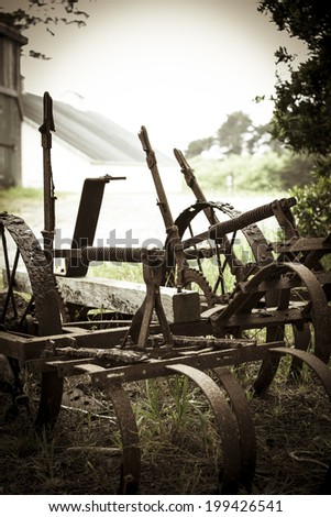 Old plow in grass by barn - stock photo