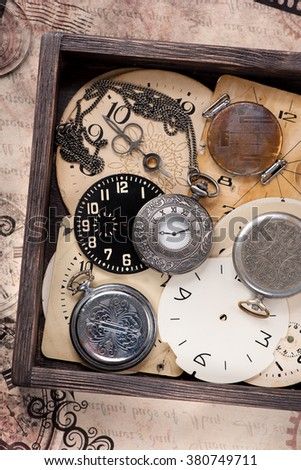 Old pocket watch and clock face in vintage box - stock photo