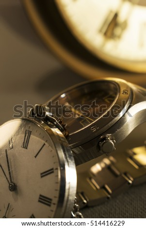Old pocket watch and modern watch in close-up view with old wall clock in background