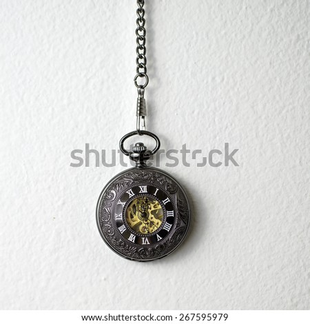 Old pocket watch hanging on the white wall - stock photo