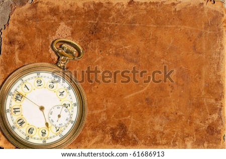 Old pocket watch laying on a worn leather background - stock photo