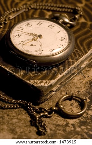 old pocket watch on a old worn book - stock photo