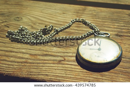Old pocket watch on a wooden background - stock photo