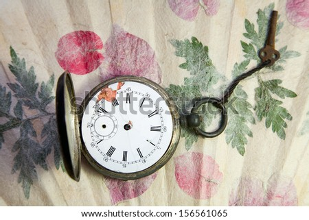 old pocket watch on handmade paper with leaves - stock photo
