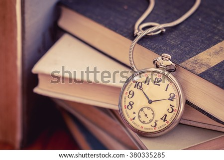 Old pocket watch on stack of books, time to read - stock photo