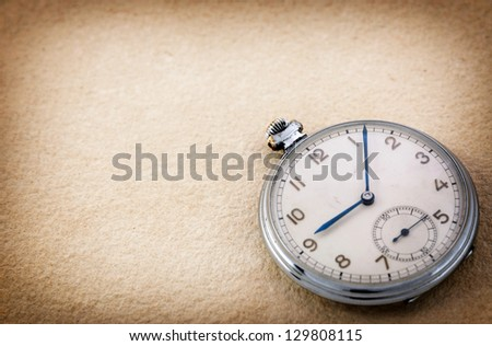 Old pocket watch on vintage paper - stock photo