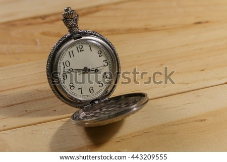 old pocket watch, vintage antique pocket watch on wooden background ,Dress light blur  - stock photo