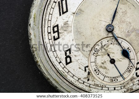 Old pocket watch with a scratched face showing the second hand pointing to twenty five seconds