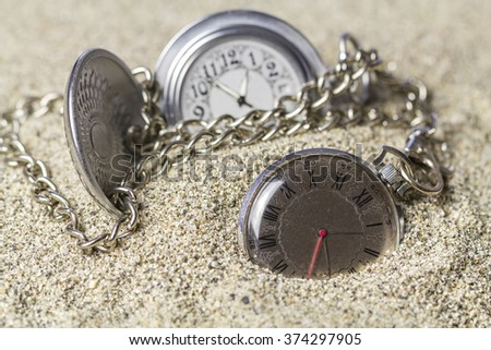 Old pocket watches with dials of various styles lie on the sand. - stock photo