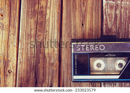 Old portable cassette player on a wooden background. image is instagram style filtered  - stock photo