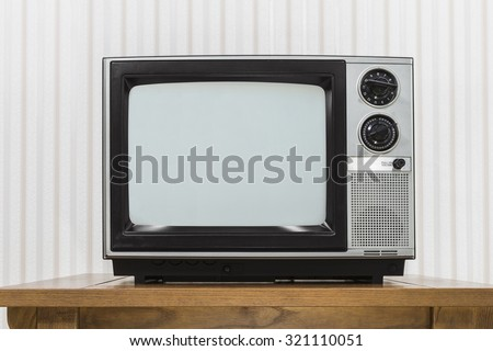 Old portable television set on vintage wood table.   - stock photo