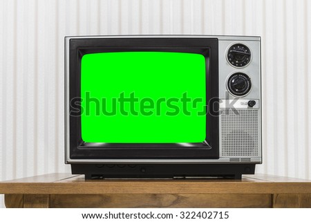 Old portable television set on vintage wood table with chroma key green screen.   - stock photo