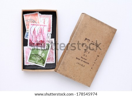 old postage stamps in a cardboard box on white background