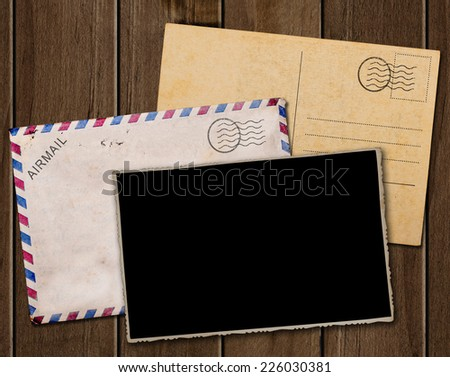 Old postcard, photo and envelope on wooden table. - stock photo