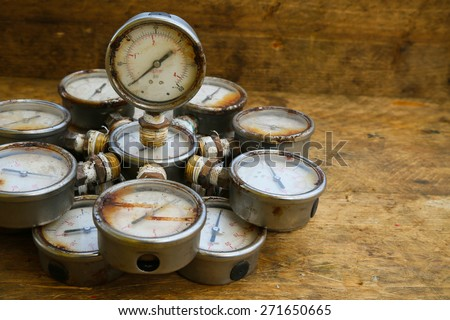 Old pressure gauge or damage pressure gauge of oil and gas industry on wooden background, Equipment of production process. - stock photo