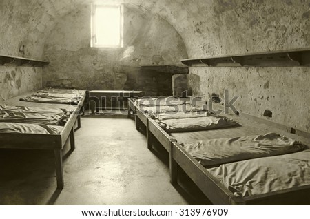 Old prison cell interior view stained duotone - stock photo