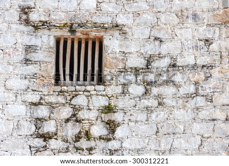 Old prison cell window with wooden bars in a white brick wall - stock photo