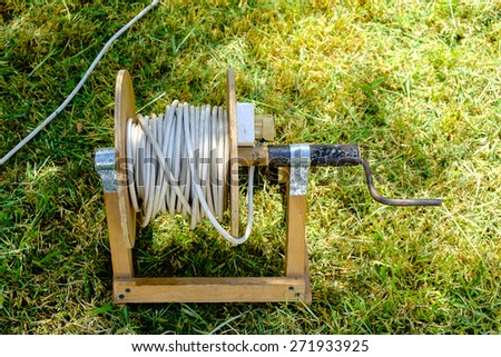 Old prolongation electric cable on green grass in the park - stock photo