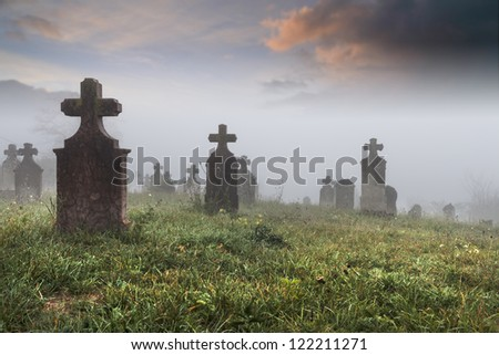 Old provincial cemetery on a cold foggy morning - stock photo