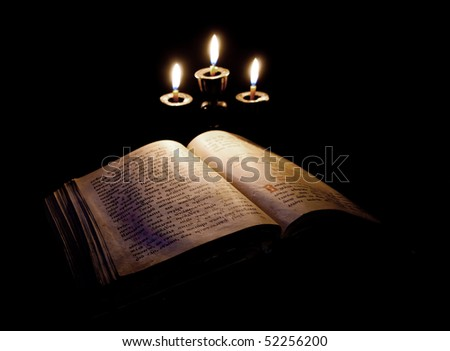 old Psalter and candles in candelabrum against black - stock photo