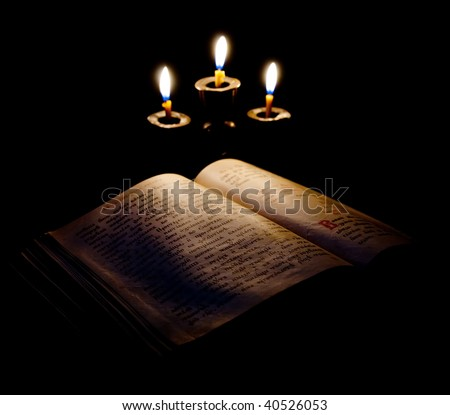 old Psalter and candles in candelabrum. Focus on book