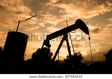 old pumpjack pumping crude oil from oil well - stock photo