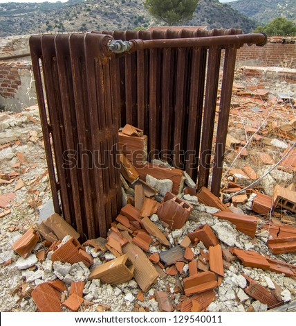 old radiator rusted among the ruins of a building - stock photo