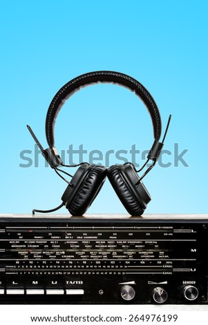 old radio with headphones on blue background - stock photo