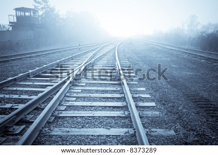 Old rail road in morning fog. Blue filtered image.