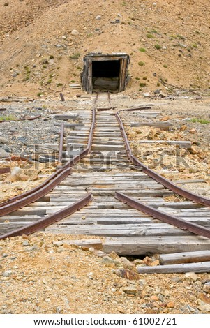 Old rail tracks leading to  an abandoned mine shaft in Yukon Territory - stock photo