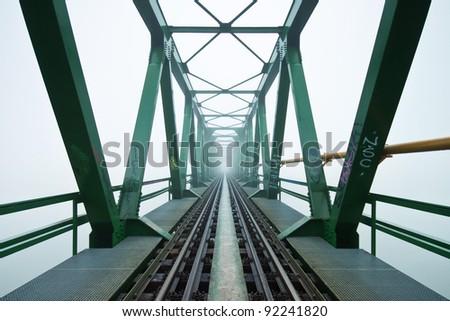 Old railroad bridge in fog - stock photo