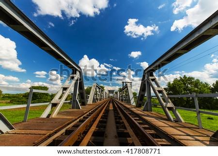 Old railroad bridge profiled on blue sky in summer - stock photo