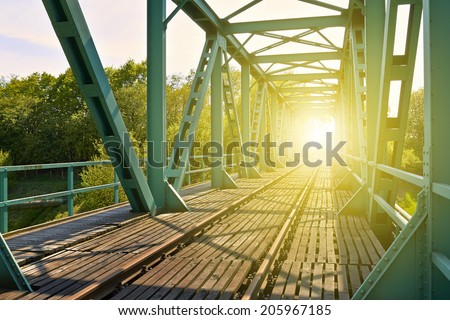 Old railway bridge with truss structure and bottom-mounted roadway. - stock photo