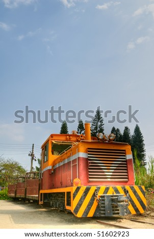 Old railway engine in orange color under blue sky. - stock photo