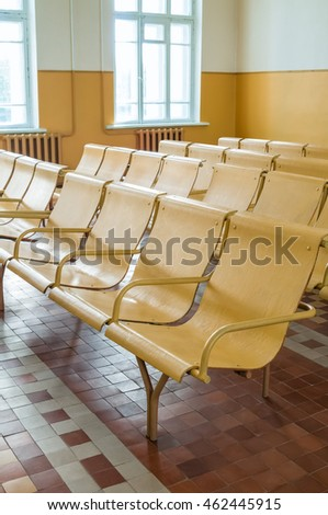 Old railway station waiting room with empty chairs.
