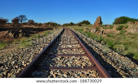 Old railway through arid African landscape - stock photo