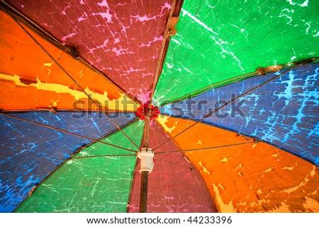 Old rainbow umbrella in southeast asia market. - stock photo