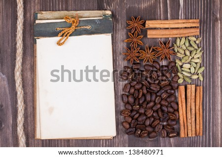 Old recipe book, coffee, cinnamon, star anise, cardamom, rope on wood background - stock photo
