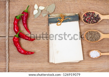 Old recipe book, red chili pepper, spices, garlic, bay leaf on oak wood texture background - stock photo