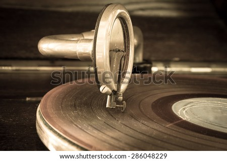 Old record player stylus on a rotating disc,vintage filtered. - stock photo