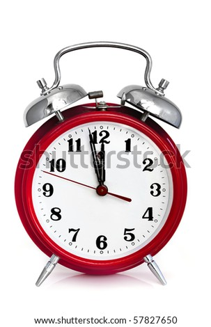 Old red alarm clock, showing two minutes to midnight.  Isolated on white. - stock photo
