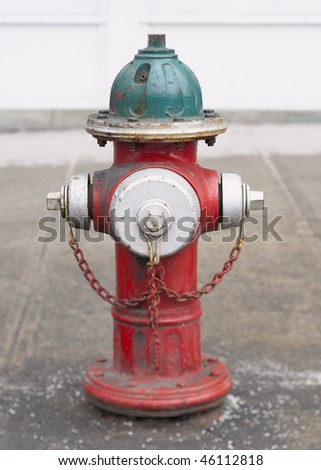 Old red and green fire hydrant in street - stock photo